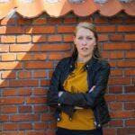 Lisbeth Lauritsen foran mur